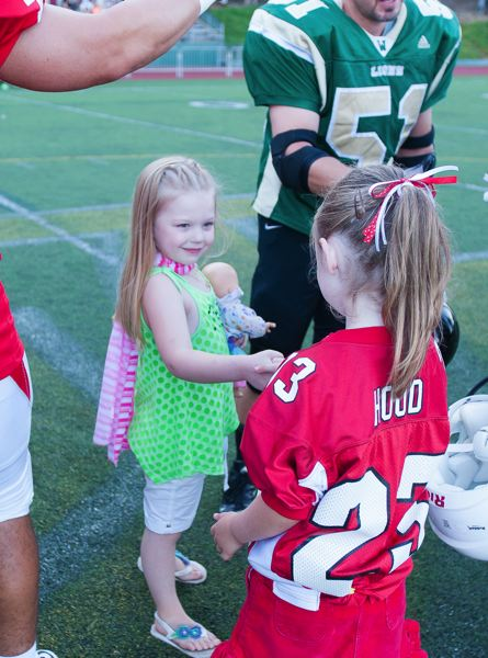 by: JOSH KULLA - Honorary captains Sophia Giammanco (left) and Josephine Clark shake hands prior to the Battle for the Bridge game.