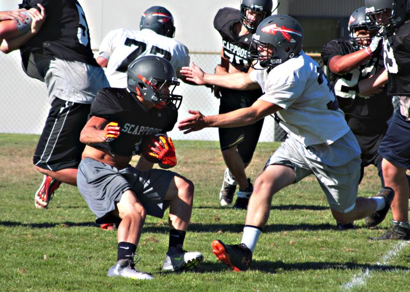 by: JOHN WILLIAM HOWARD - Running back Carson Davison (at left in black) spins past a defender on Tuesday afternoon. Davison has continued to be impressive both on the run and when asked to pick the ball out of the air.