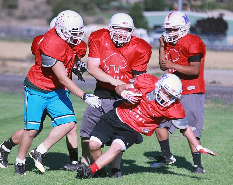 by: BILLY GATES/THE PIONEER - A group of Madras High School defensive linemen swarm to the ball carrier during Monday's practice at Madras High School.