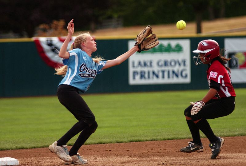 by: DAN BROOD - CAUGHT STEALING -- Tualatin City shortstop Camille Hall (left) reaches for the ball before tagging out Philippines' Jaimalyn Arnbong in last week's seventh-place game at the Little League Softball World Series. The Tualatin City team went 2-3 at the series.