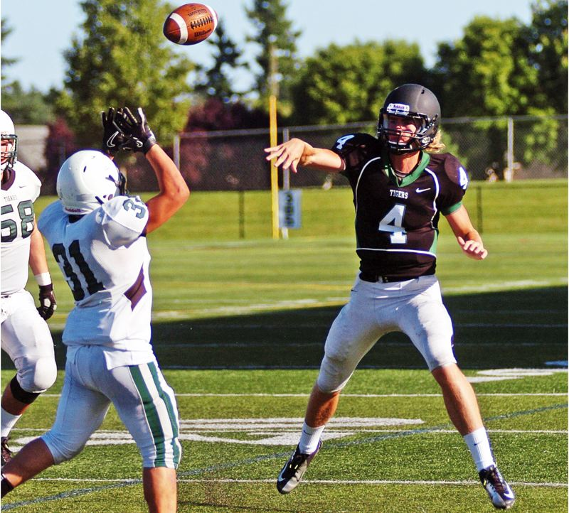by: DAN BROOD - FINE FORM -- Tigard QB Jett Even (right) throws a pass in June's Chicken and Bean Bowl.