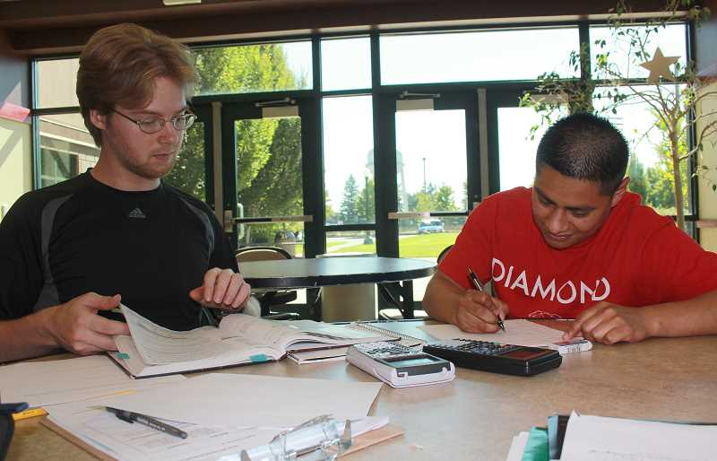 by: JEFF MCDONALD - Jared Bynum, a second-year student at Chemeketa Community College, helps Alvaro Mendoza, 22, study for an algebra exam in the schools cafeteria in Woodburn last week. Bynum is working for his associate degree.