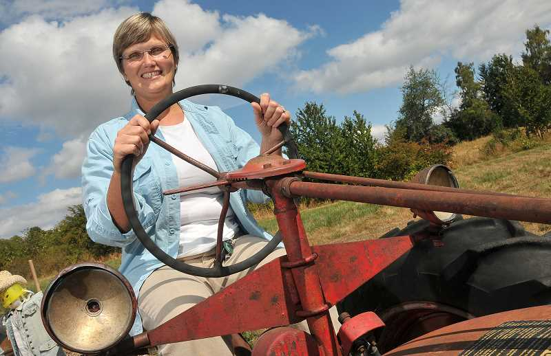 by: VERN UYETAKE - Dawn Grunwald, Children's Garden coordinator at Luscher Farm, has been making good use of the farm's remodeled classic tractor this summer.