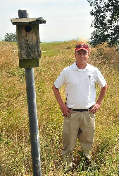 by: VERN UYETAKE - Superintendent Russell Vandehey tends to the bluebird nesting boxes at Oregon Golf Club.