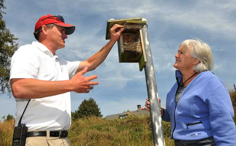 by: VERN UYETAKE - Russell Vandehey and bird bander Elaine Newland check out another avian abode.