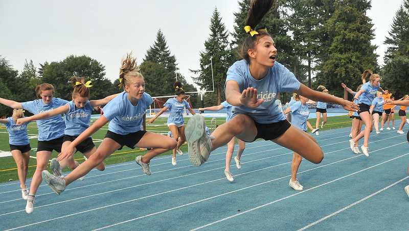 by: REVIEW PHOTO: VERN UYETAKE - Lakeridge High School cheerleaders jump into action during practice last week.