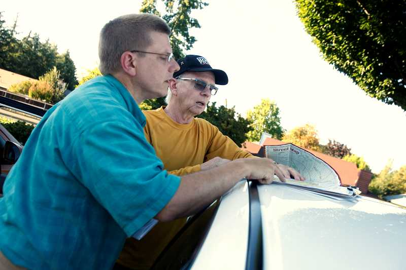 by: TIMES PHOTO: JONATHAN HOUSE - Tim Esau and Andy Bergman go over Tigard neighborhood maps to find the best spots to petition to stop light rail from coming into Tigard.