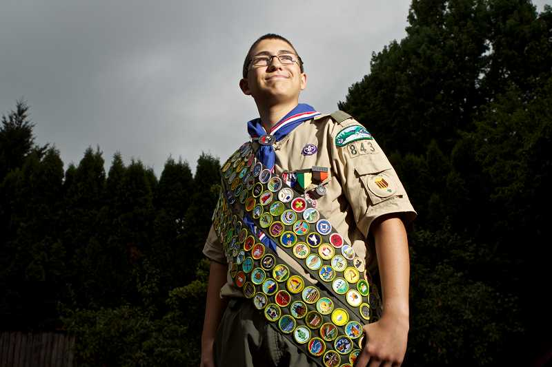by: TIMES PHOTO: JAIME VALDEZ - George Christensen, an 15-year-old Eagle Scout with Troop 843 in Tigard, dons his sash of 137 merit badges. Christensen has earned every merit badge available, and is one of 200 to have ever earned them all.