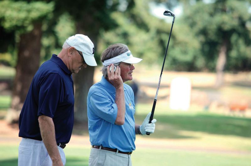 by: TRIBUNE PHOTO: JONATHAN HOUSE - Ron Plath (right) of Lake Oswego listens to a GPS device to determine yardage to the pin during last weeks United States Blind Golf Association national championship at Stone Creek Golf Club in Oregon. Stone, with coach Regi Christensen (left) won one of the division titles and was inducted into the USBGA Hall of Fame.