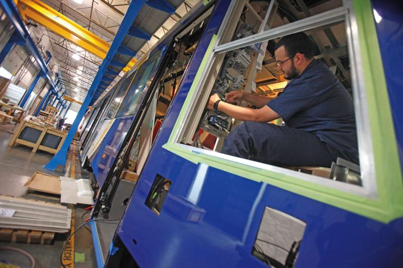 by: TRIBUNE PHOTO: JONATHAN HOUSE - United Streetcar technician Alvaro Sanchez wires a new car at the companys assembly plant in Clackamas.