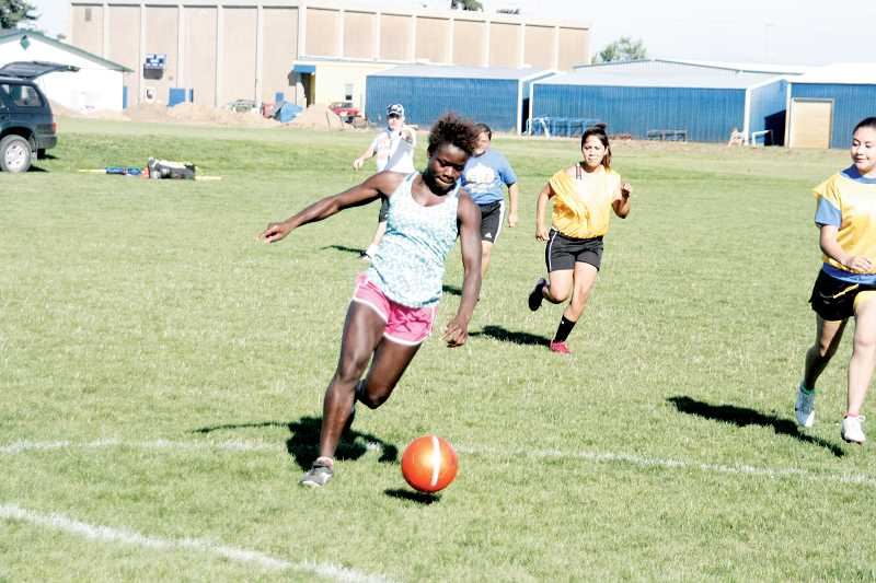 by: PHIL HAWKINS - Mulkerin directs from the back of the field as senior Beverlyn Stott dribbles the ball toward the goal.