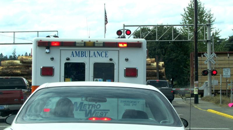 by: MARK MILLER - Traffic, including a Metro West ambulance, sits at the interchange of St. Helens Street and Highway 30 in north St. Helens while waiting for a log train to clear the railroad crossing.