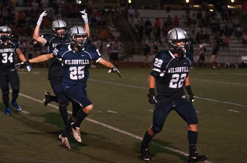 by: SPOKESMAN PHOTO: JOSH KULLA - Wilsonville defensive back Nathan Burke (22) intercepted two passes Friday against Sprague, here he and teammates celebrate the second, which came in the fourth quarter.