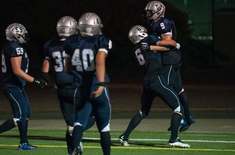 by: SPOKESMAN PHOTO: JOSH KULLA - Wilsonville junior linebacker Lane Hull (right) is mobbed by teammates after scoring on an 11-yard interception return in the third quarter of Fridays 23-7 win over Sprague.
