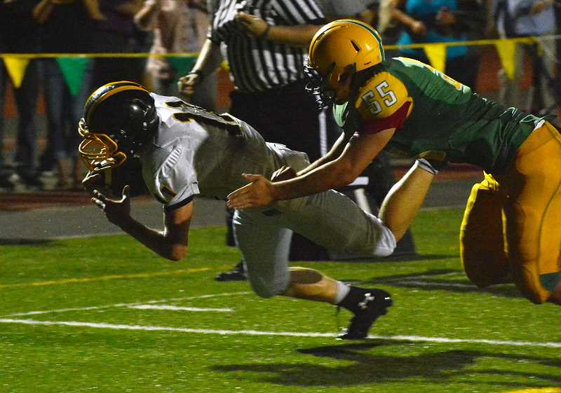 by: JOHN WILLIAM HOWARD - St. Helens running back Tanner Long dives for the end zone in the third overtime of the football game on Friday, Aug. 30. Long missed the touchdown by a yard, but the Lions scored on the next play to take a 35-27 lead.