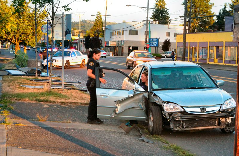 by: DAVID F. ASHTON - An East Precinct District officer talks with the driver of the Honda which plowed through a TriMet bus shelter, smashing it to bits, on S.E. Foster Road. Thats whats left of the shelter, on the parking strip, behind at left.