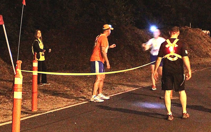 by: DAVID F. ASHTON - At just past midnight on August 24th, Bill Galante gets ready to hand off his teams wrist band to George Henderson on the Springwater Trail, in the Ardenwald-Johnson Creek neighborhood, during the 2013 Hood to Coast Relay.