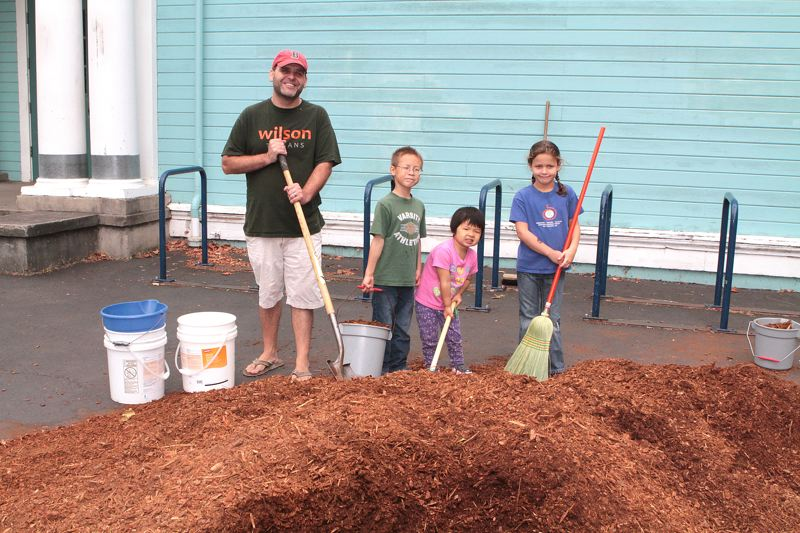 by: DAVID F. ASHTON - New Woodstock Elementary School Principal T.J. Fuller, along with students Andrew and Aliya Kobus and Lucy Weinberg, dig in - to mulch the flowerbeds at the school on August 24th.