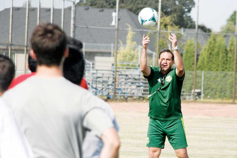 by: PHIL HAWKINS - Baker lofts the ball in a header drill at practice during the opening two weeks before the beginning of the season.
