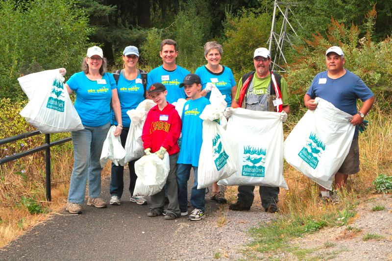by: DAVID F. ASHTON - The Chair of Friends of Tideman Johnson Park, Marianne Colgrove (far left), stands with volunteers on the Springwater Trail who have already gathered bags of trash during the first hour of the 2013 Johnson Creek Clean Up, on August 24th.