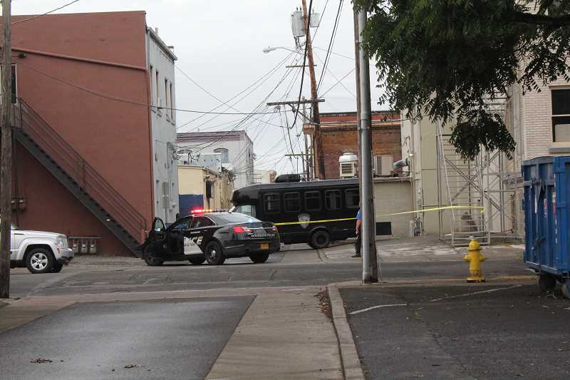 by: LINDSAY KEEFER - Police block off the alleyway along Lincoln Street between Front and First streets Tuesday morning while investigating the death of an unidentified adult male.