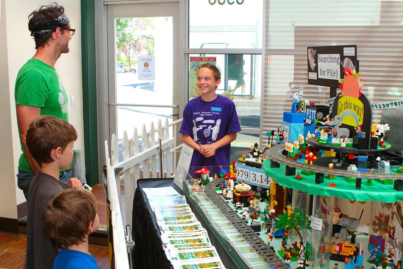 by: DAVID F. ASHTON - Christopher B. answers guests questions about the Searching for Pi (or Pie) LEGO Logo Board construction that was the centerpiece of the display at the Division-Clinton Street Fair again this year. It took many students several months to design and build. It is not a kit!