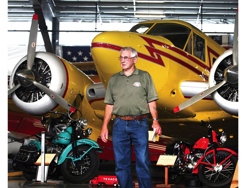 by: JIM CLARK/PAMPLIN MEDIA GROUP - WAAAM member and volunteer Dick Clarke poses in front of a 1957 Beech E18S corporate plane, which is on loan. The aircraft, which holds seven passengers and two crew members, is one of Clarkes favorite planes on display at WAAAM.
