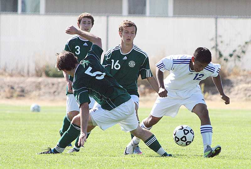 by: PIONEER FILE PHOTO - Madras' Maylo Urieta (12) tries to work past defenders from Summit during a match last year. Urieta, a junior, will be one of the White Buffalos' key players this year in the midfield.
