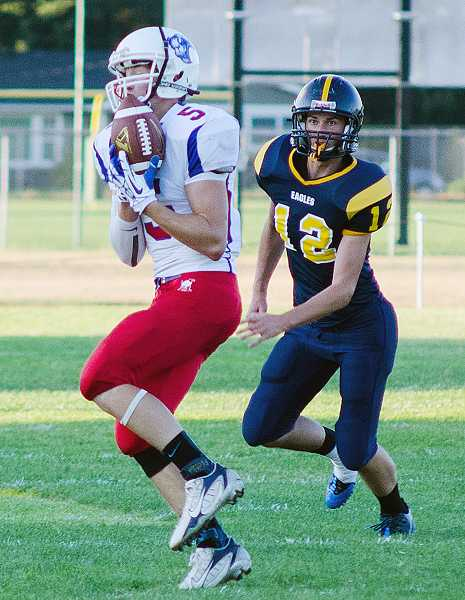 by: CRAIG LASH/SMALL TOWN SPORTS NETWORK - Madras' Cody Shepherd (5) hauls in one of his five receptions against Stayton on Friday. Madras picked up the win, 21-20.