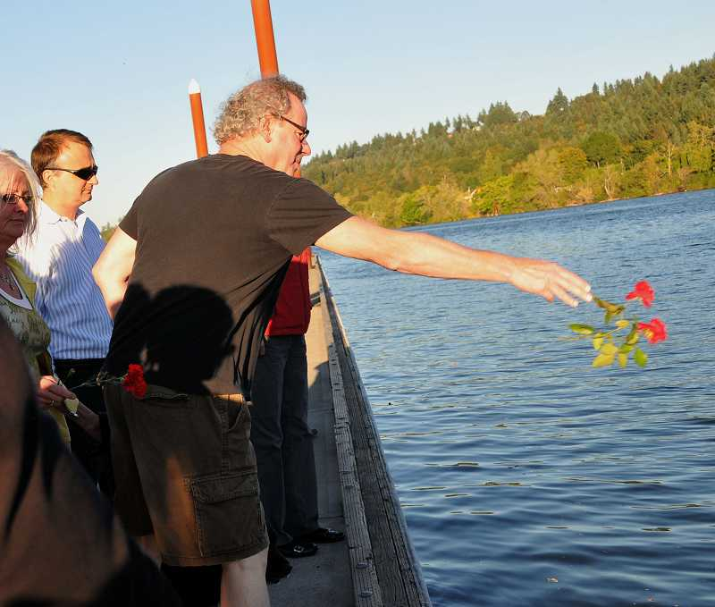 by: TIDINGS FILE PHOTO: VERN UYETAKE - After a wreath is tossed into the river, community members throw their own commemorative flowers.