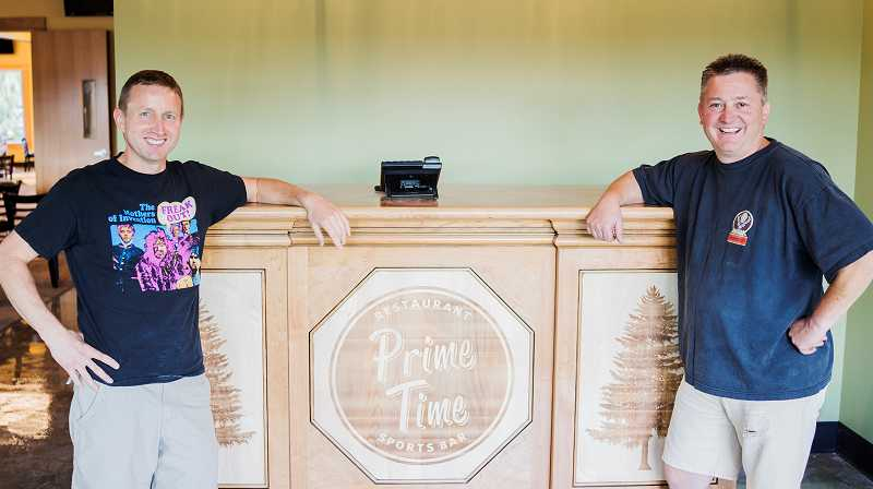 by: NEWS-TIMES PHOTO: CHASE ALLGOOD. - Prime Time co-owners Ed Gilbertz (left) and Greg Jansen stand at the rebuilt restaurants front desk, made by local business F & C Cabinets and laser etched with the restaurants logo. Its just absolutely gorgeous, Jansen said.
