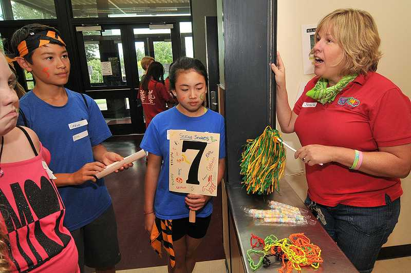 by: TIDINGS PHOTO: VERN UYETAKE - Nora Wilson, right, explains the snack shack to Graham Yotsuya and Ellie Garcia.