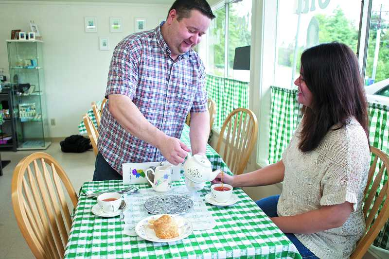 by: TIMES PHOTO: JAIME VALDEZ - Jonathan Sullivan pours his wife, Nicole, a cup of  tea at their business, Forget Me Not Ireland, a gift shop, Irish dance accessory store and tea room in Raleigh Hills.