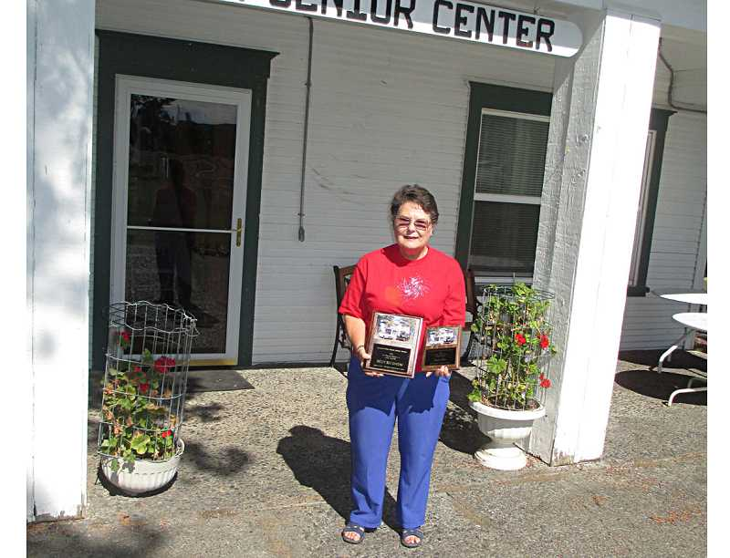 by: JOHN BOWLER - Earleen Arthur, president of the Ranch Seniors, displays the plaques to be awarded at the 50 Car Show Sept. 21.