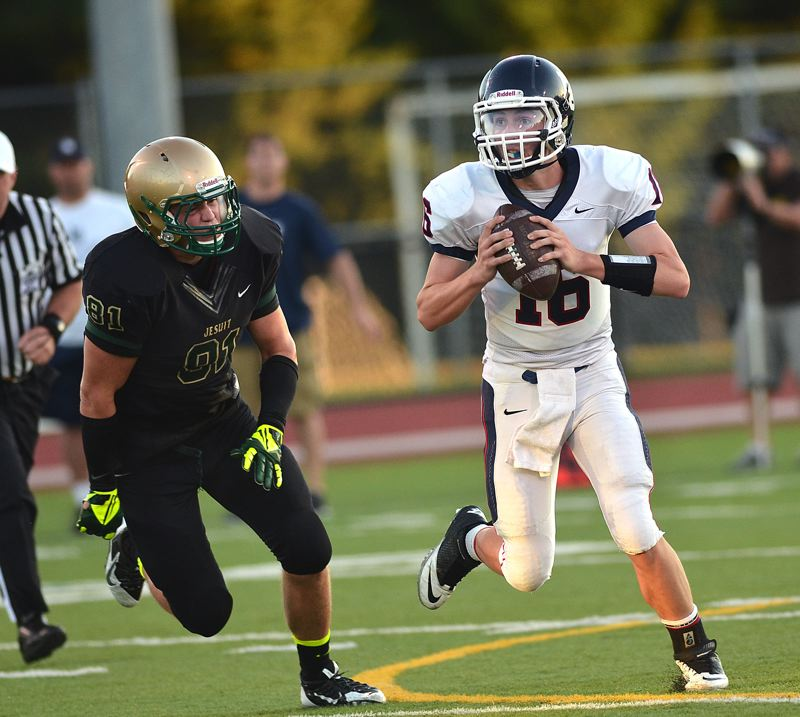 by: VERN UYETAKE - Lake Oswego quarterback Mitchell Verburg rolls away from pressure during last week's season opener against Jesuit. Verburg threw for 172 yards and a pair of touchdowns in the game.