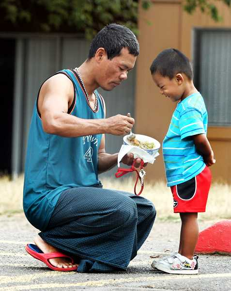 by: OUTLOOK PHOTO: JIM CLARK - Barberry Village resident Ye Mun Aung feeds his one year-old son Khant Win Aung in the complex parking lot on a recent evening. The Aung family are immigrants from Burma.