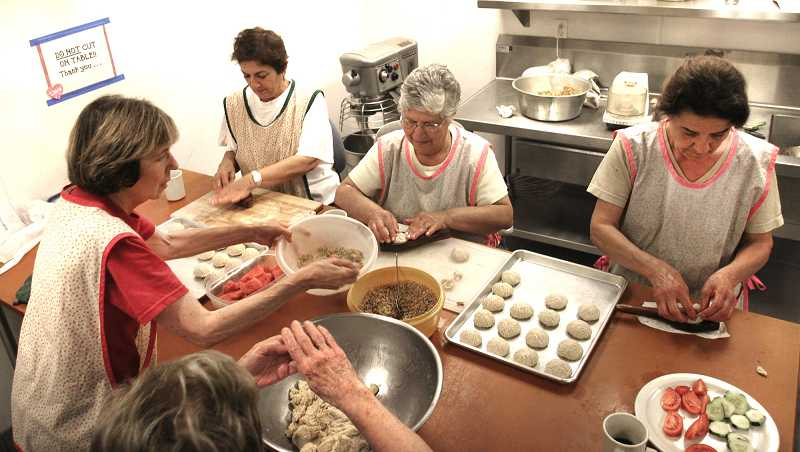 by: FILE PHOTO: JIM CLARK - Volunteers from Saint George Antiochian Orthodox Christian Church assemble date and walnut mamool in preparation for the upcoming Middle Eastern Festival in this 2011 photo.