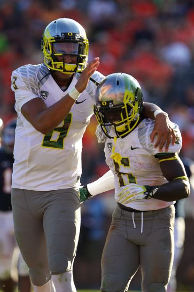 by: TRIBUNE PHOTO: JAIME VALDEZ - Oregon quarterback Marcus Mariota (left) congratulates running back De'Anthony Thomas on his third-quarter touchdown at Virginia.