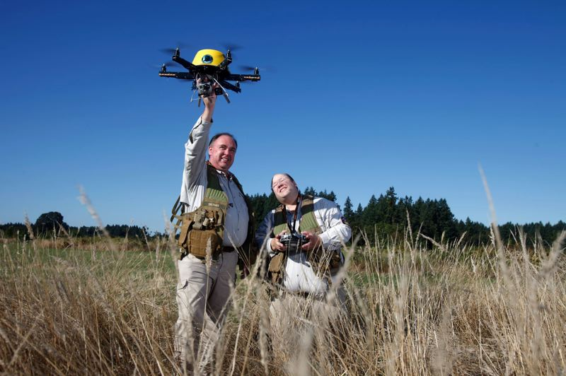 by: PHOTO BY JONATHAN HOUSE - Patrick Sherman, left, catches the drone, while Brian Zvaigzne, holding the goggles and the controller, looks on. The two men were flying the drone near a natural area in Wilsonville.