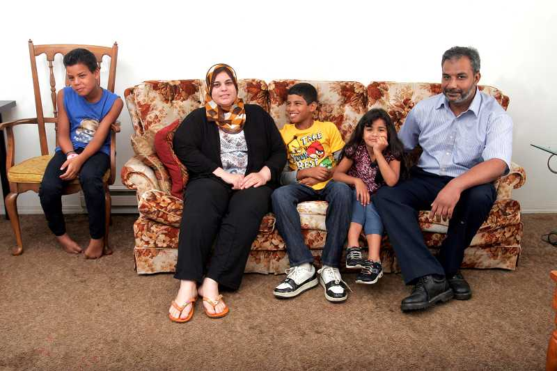 by: OUTLOOK PHOTO: JIM CLARK - Ahmed Abdullah, right, and Maryan Mohammad, second from left, moved to Barberry Village from Syria with their three children, Yassir, left, Abdul, middle, and Manahel, second from right.