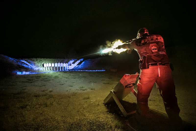 by: CRIMSON TRACE - A competitor at the Crimson Trace 3-Gun Invitational lets loose with a burst of rounds from a 5.56mm rifle. All shooting was done at night on nine different courses created for the event.