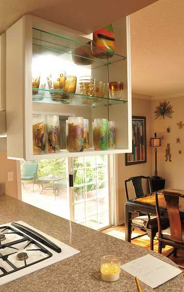 The overhead kitchen cabinet was cut and woodshelves replaced with glass shelves to give a more airy feel.
