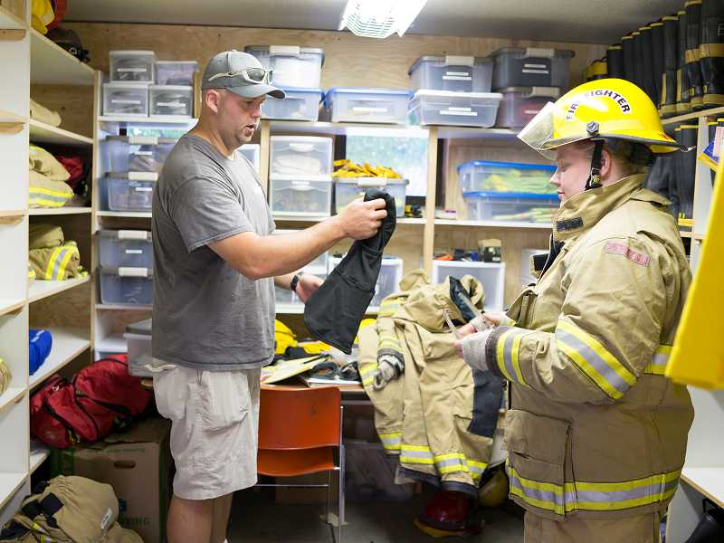 by: NEWS-TIMES PHOTO: CHASE ALLGOOD - Fire Captain Tony Carter helps outfit volunteer firefighter Jennifer Robinson with the necessary fire gear on the first day of Forest Groves training academy for new volunteers.