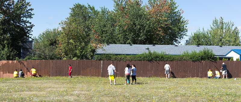 by: NEWS-TIMES PHOTOS: CHASE ALLGOOD - Paintover volunteers spread out along a 500-foot-long fence bordering a sports field at Neil Armstrong Middle School. (L-R): DeMolay volunteer Travis Hendershott, 13, and his friend Tyson; Gabriel Jones, 17; Alex Rojas-Lopez, 9; Allyn Clark; Celia Lopez; Maria Lopez; Rick Clark; Dakota Crosby, 15; Chris Crosby, 17; Jason Thacker.