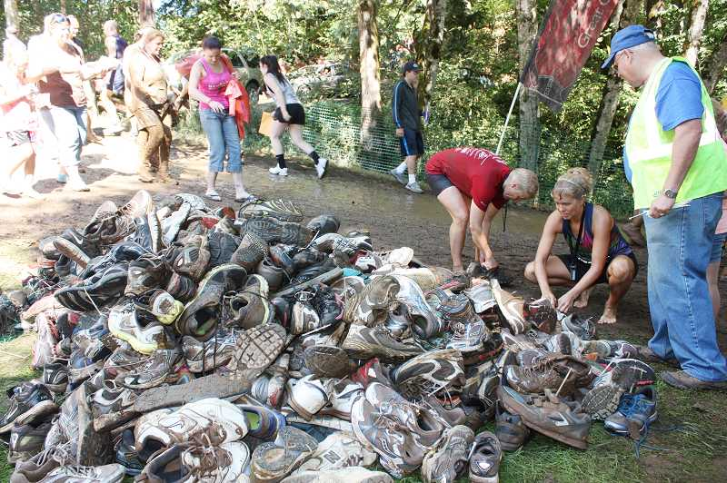 by: NEWS-TIMES PHOTO: DOUG BURKHARDT - Steve Johnson (right), a community recycling specialist for USAgain, watches a massive pile of running shoes grow larger and larger as Warrior Dash competitors stop to leave their muddy shoes after participating in the 5k obstacle course.