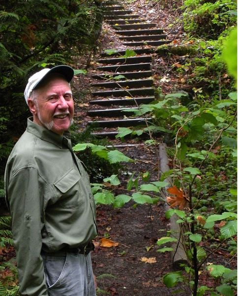 by: POST PHOTO: JIM HART - Jim Slagle stands near the trail he designed and built in the early 1980s, leading into Meinig Park from the Park Crest neighborhood, where he lives. The stairs were installed when he was adviser to an Eagle Scout trail improvement project about 15 years ago.