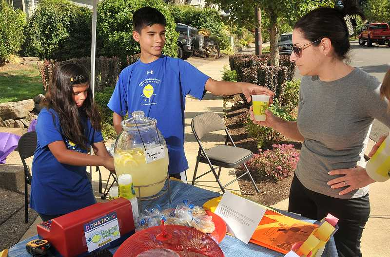 by: TIDINGS PHOTO: VERN UYETAKE - Customers enjoy cold drinks at the Rowers lemonade stand on Aug. 27.