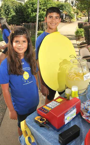 by: TIDINGS PHOTO: VERN UYETAKE - Karina Rower, 8, handles the cash register while Alex Rower, 12, wears a handmade lemon costume.