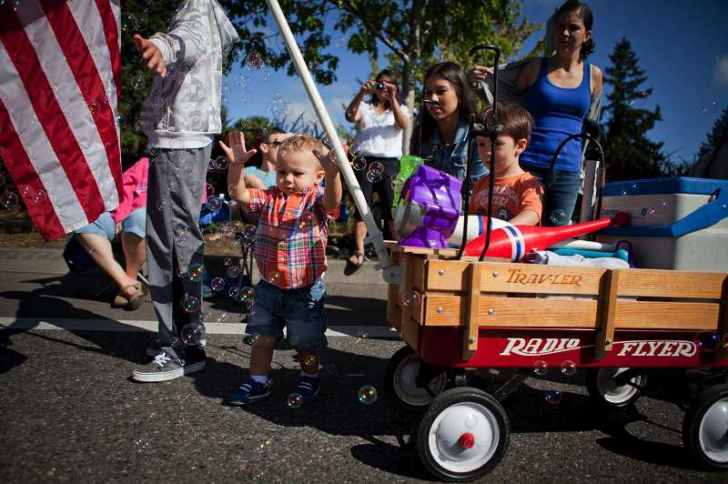 by: TIMES PHOTO: ADAM WICKHAM - Aden Carolla, 1, of Beaverton plays with bubbles at the 56th annual Beaverton Celebration Parade that marched through downtown on Saturday.