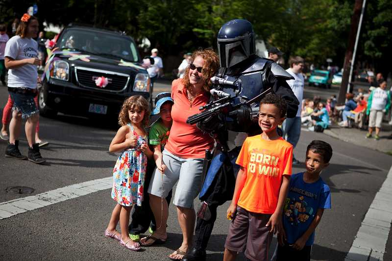 by: TIMES PHOTO: ADAM WICKHAM - Parade attendees pose for a photo with a member of the Mandalorian Mercs costume club.